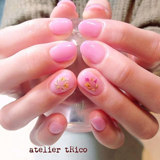 ベビーピンクのワンカラーネイルにお花が可憐に咲いている...