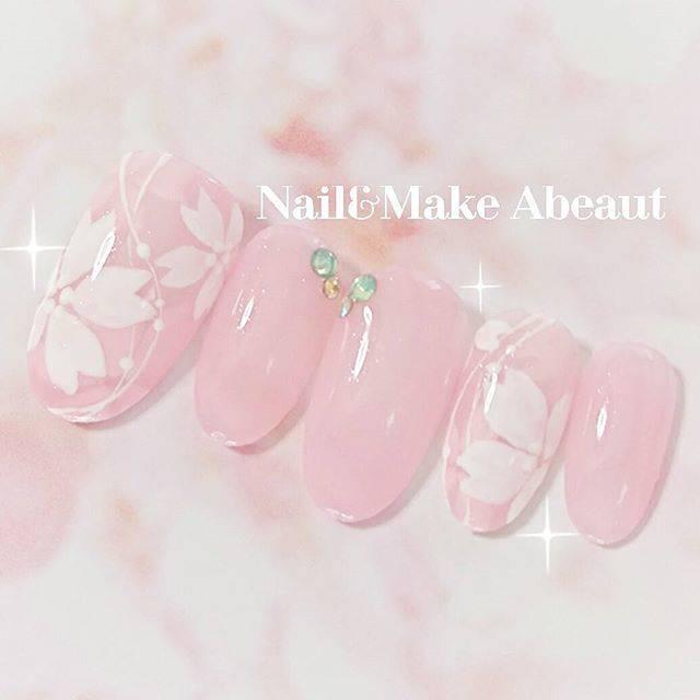 ピンクカラーのワンカラーネイルに桜モチーフをプラスした...