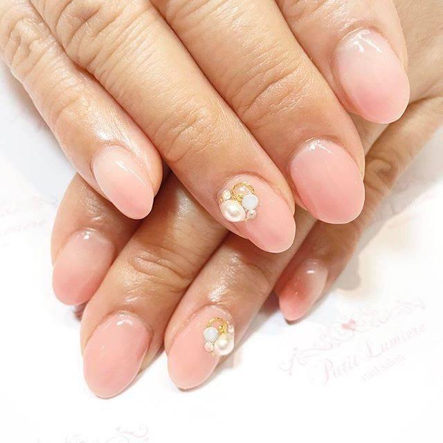 ほんのり桜色のネイルにパールのワンポイントがかわいい♡...