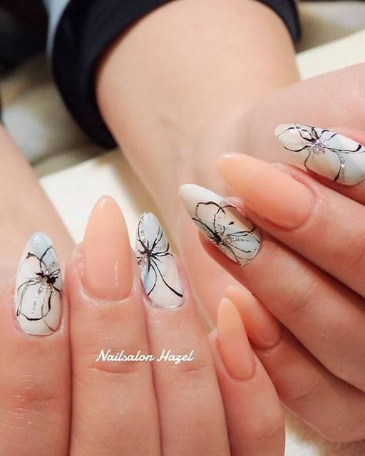 爪全体を使って大きく描かれた大輪の花がフェミニンなネイ...