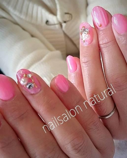 明るいピンクを基調にしたネイルは手元をパキッと明るく魅...