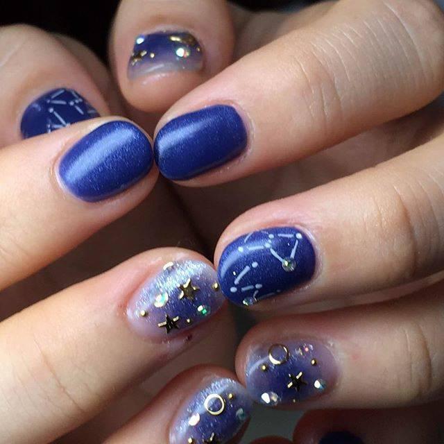 マットなブルーのネイルに星空と星座が描かれているデザイ...